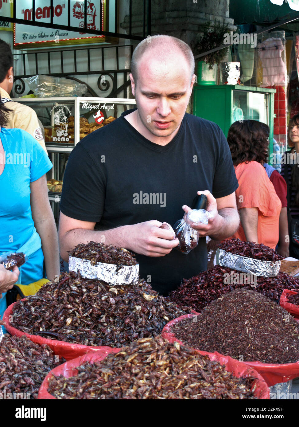 young tourist with stubble beard  considers purchase of fried grasshoppers (chapulinas) from sidewalk vendor Oaxaca - Stock Image