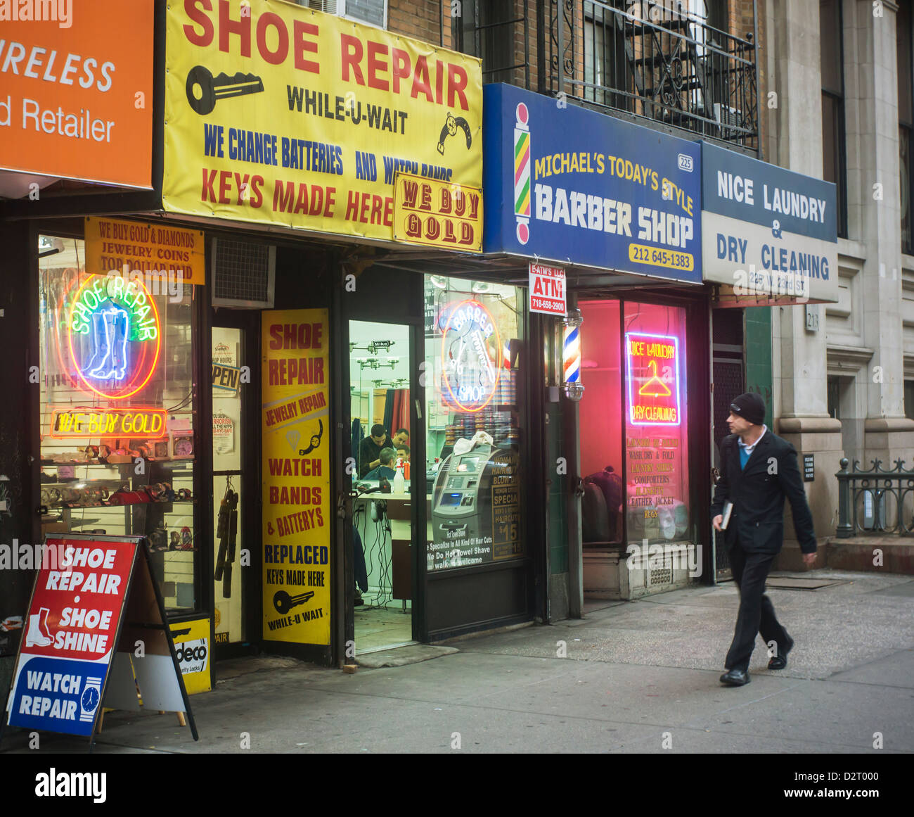 Mom and Pop small businesses, a shoe repair, a barber and a laundry, in the New York neighborhood of Chelsea - Stock Image