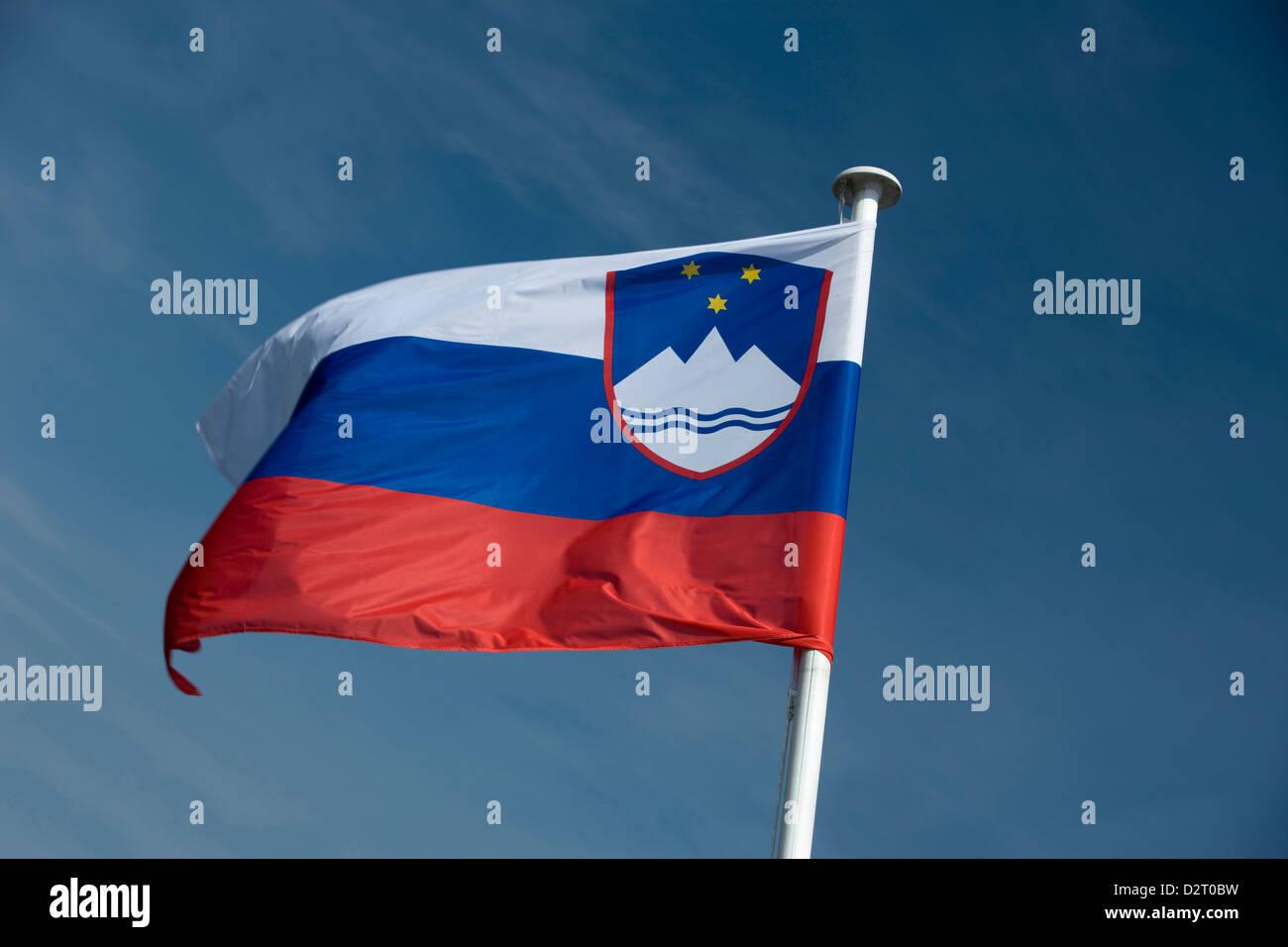SLOVENIA FLAG FLYING ON FLAGPOLE - Stock Image