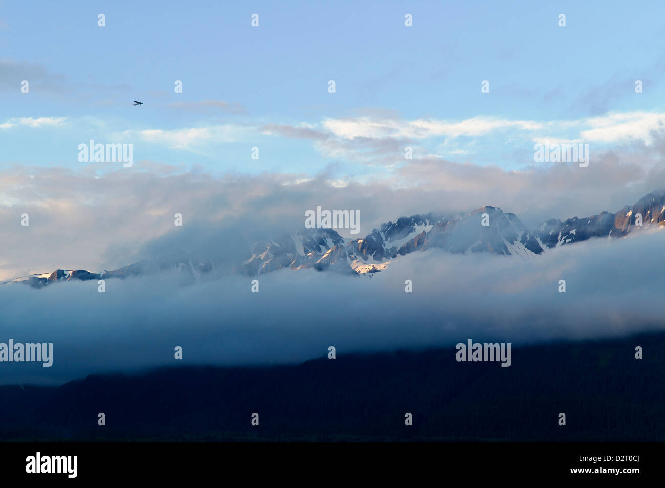 Small airplane flying through clearing skies and Chugach Mountains across Resurrection Bay, Seward, Alaska, USA - Stock Image