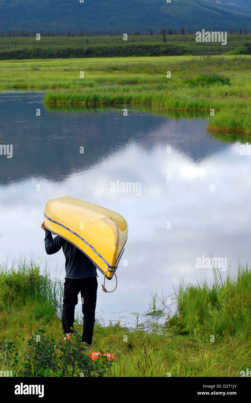 Carrying a canoe to the Moose Ponds at the start of a canoe trip on the Nahanni River in Canada's Northwest - Stock Image
