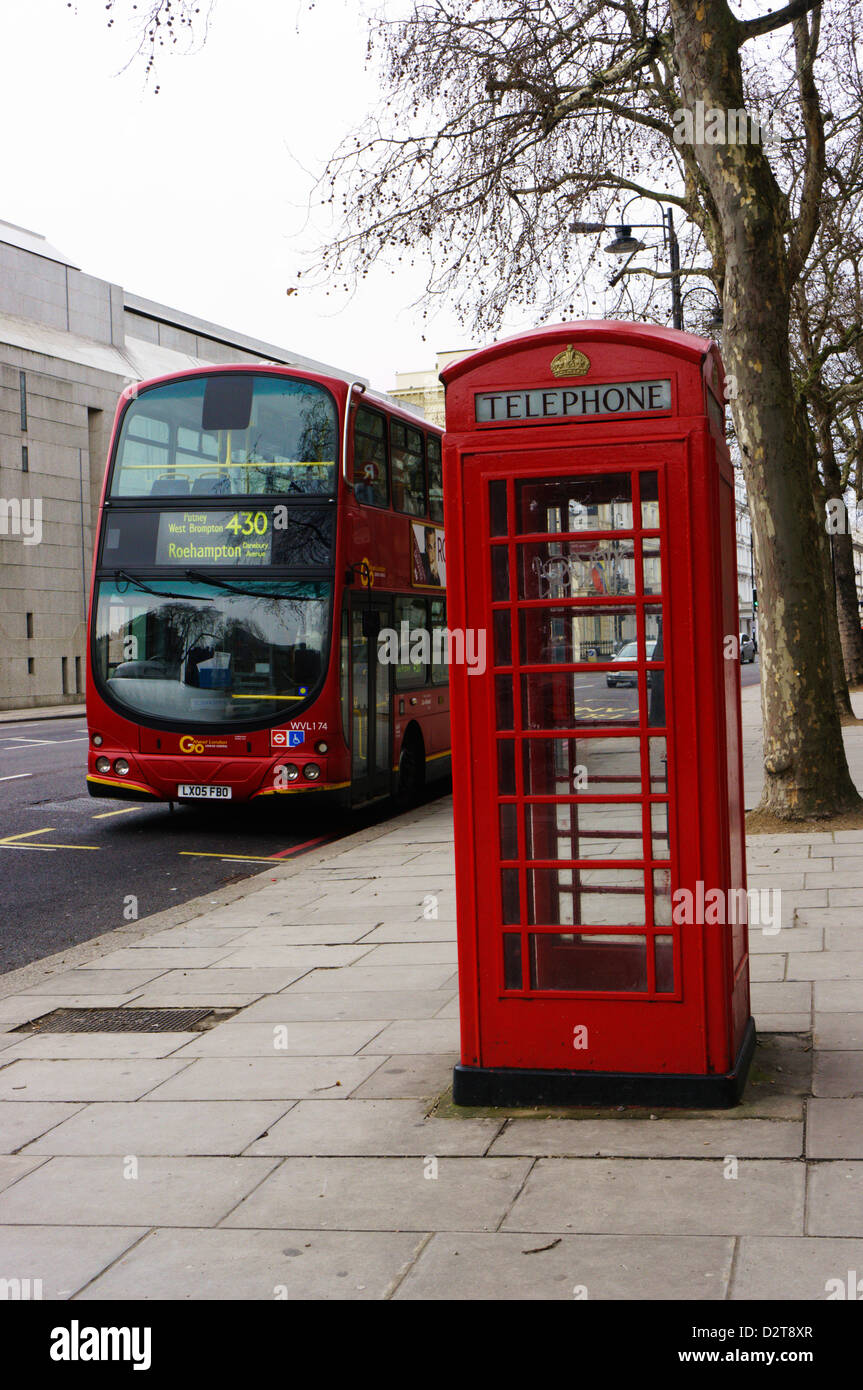 A typical K6 model London telephone box in front of a Volvo red London bus. - Stock Image