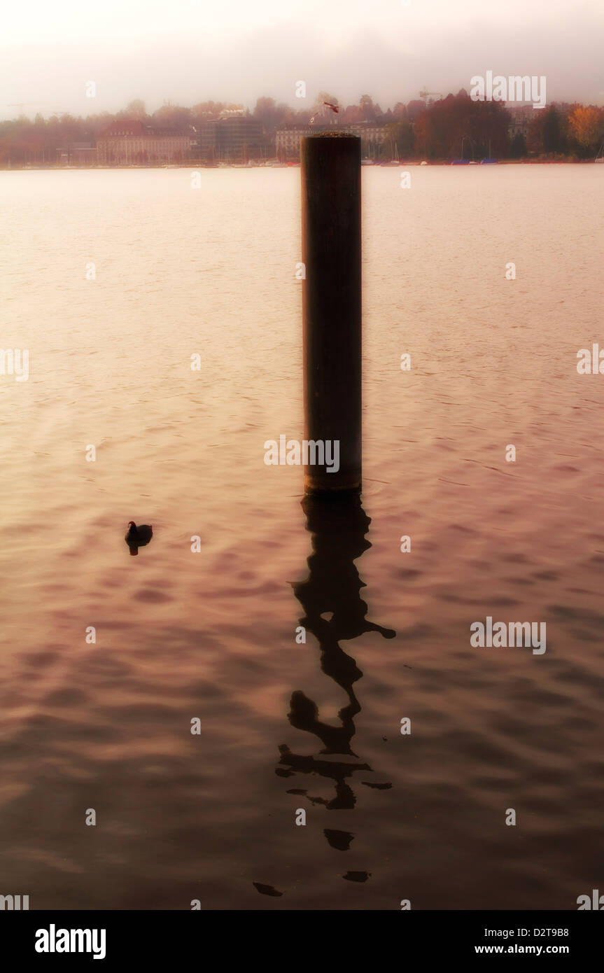 Sunset along the lake of Zurich with a post and reflection - Stock Image