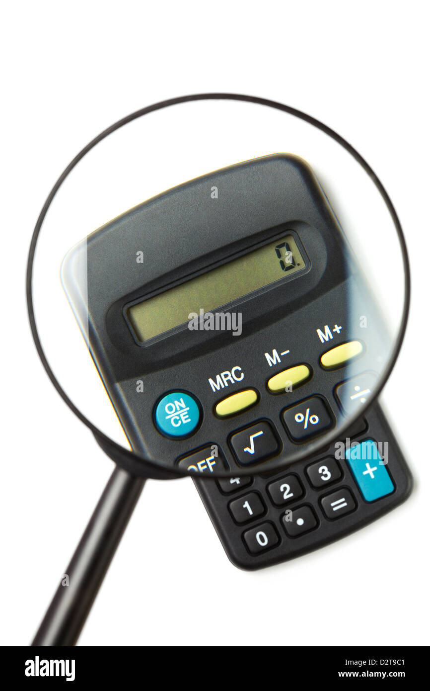 Calculator viewed through magnifying glass on white background - Stock Image