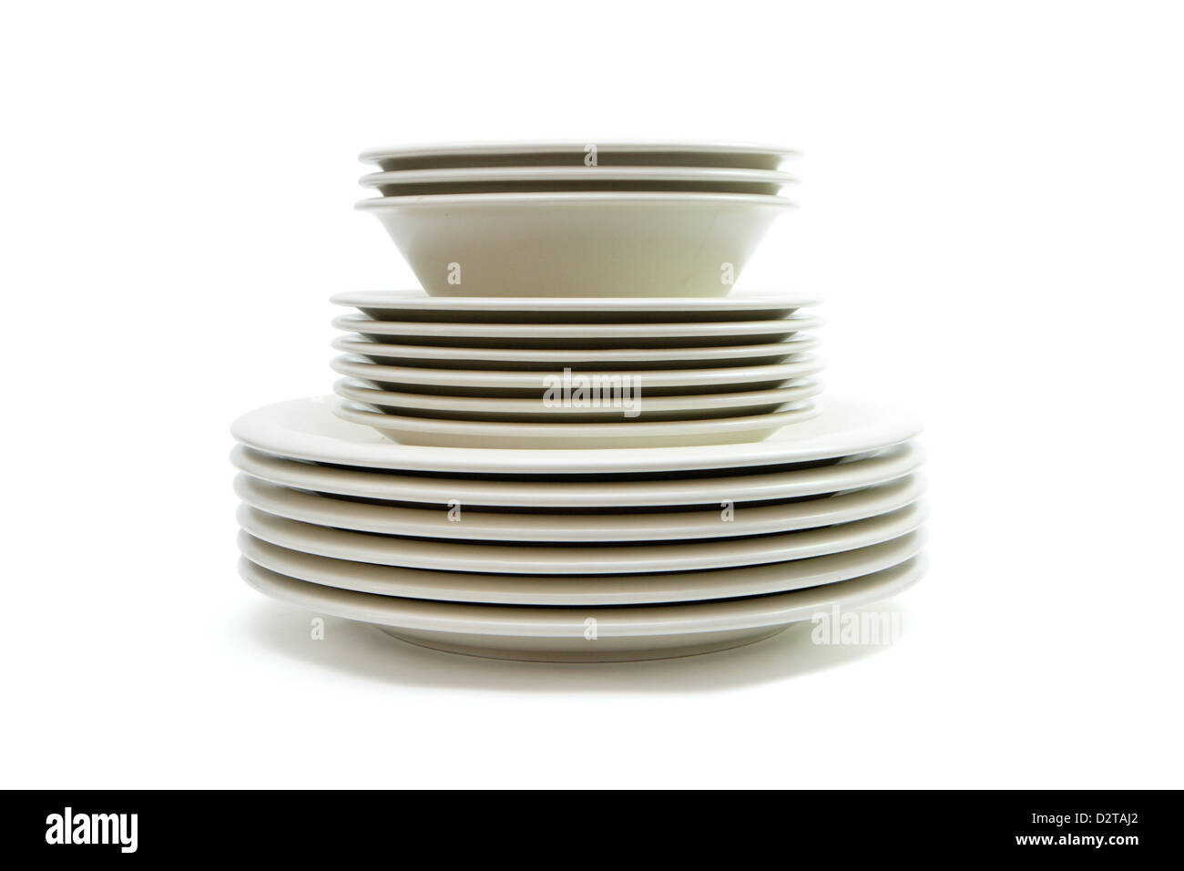 Stack of plain beige dinner plates, soup plates and saucers isolated - Stock Image