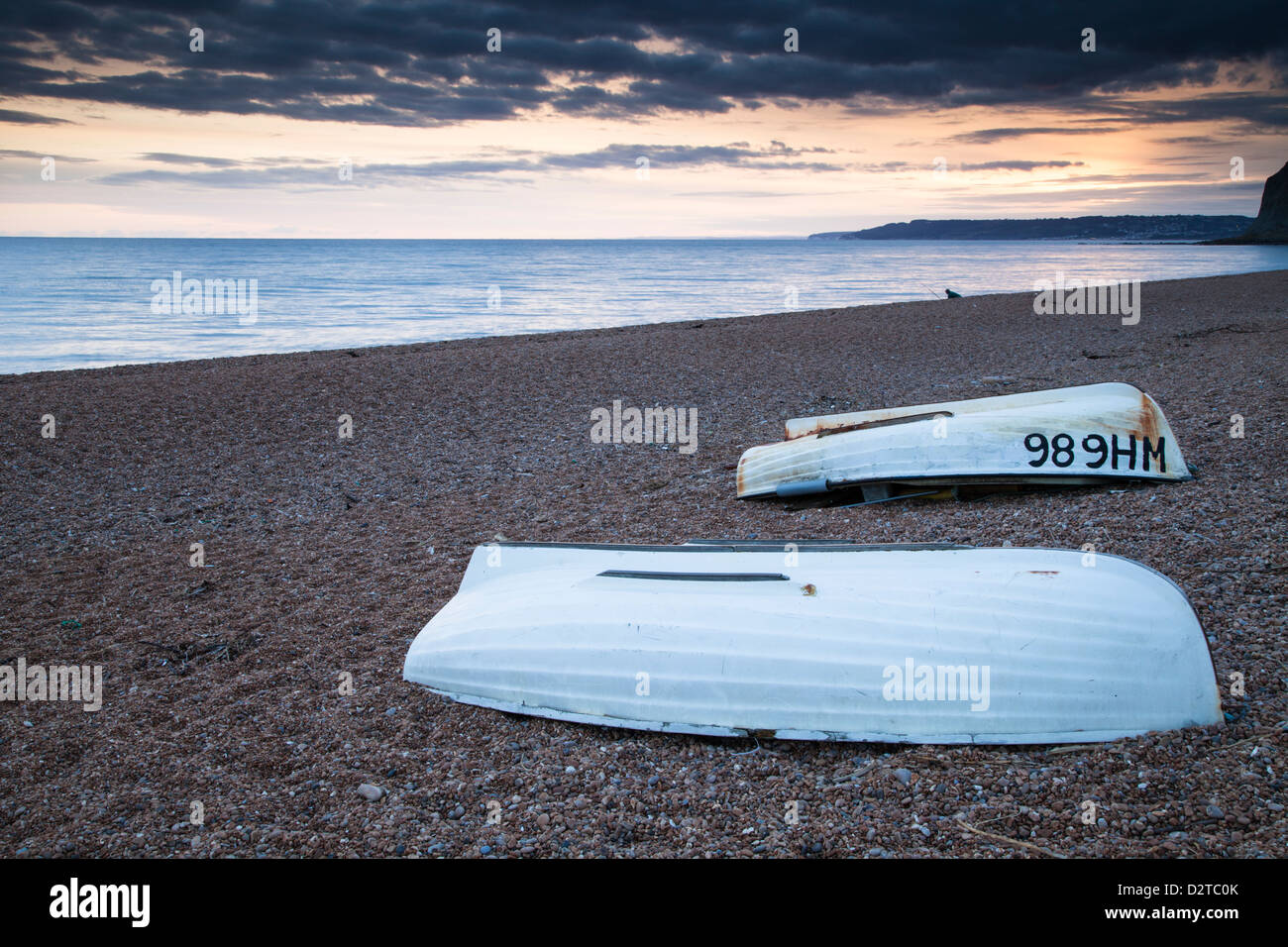 A pair of upturned wooden fishing boats on Seatown's shingle beach as the sun sets over Lyme Regis and Lyme Bay Stock Photo