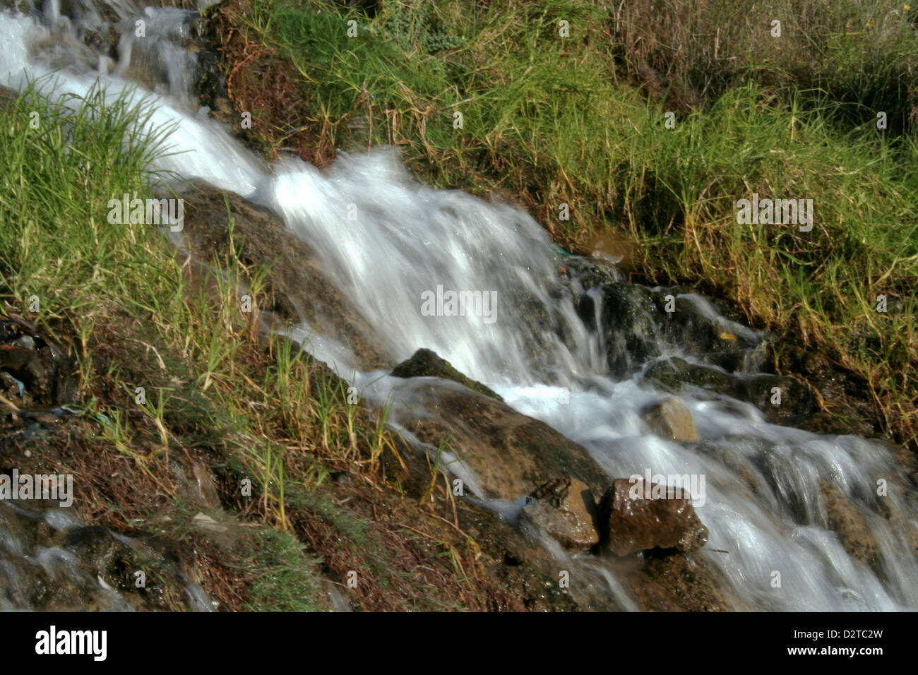 Blurred view of water rushing down the slope of mountain - Stock Image