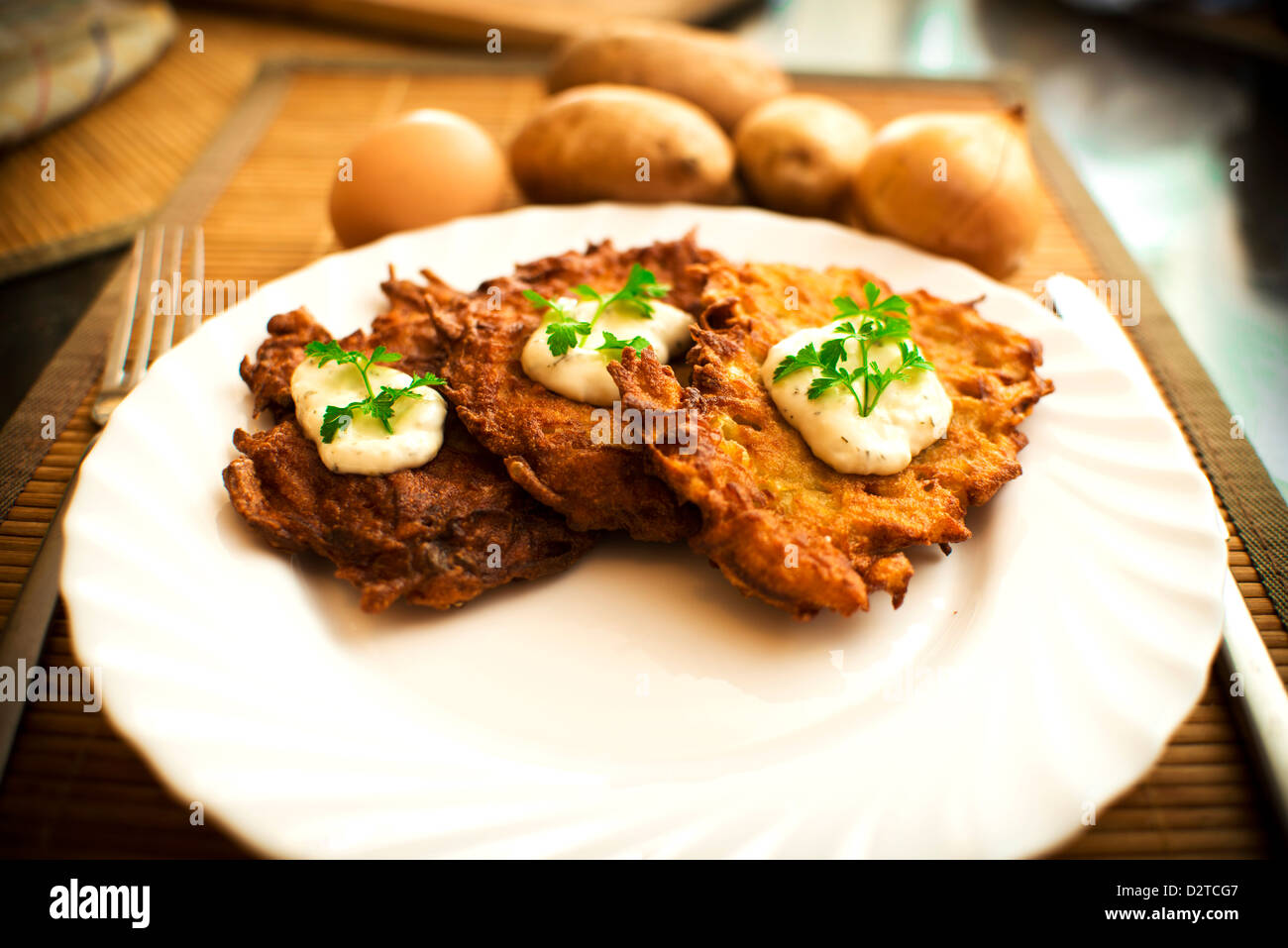 potato pancake with sour cream and parsley - Stock Image