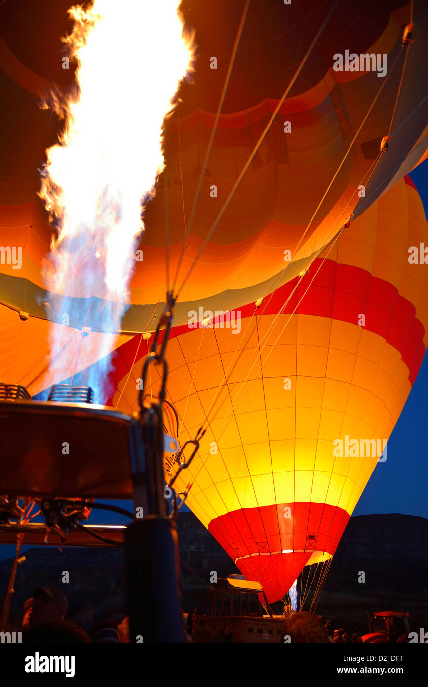 Red glow of blasts from propane heaters inflating hot air balloons at dawn Cappadocia Turkey - Stock Image