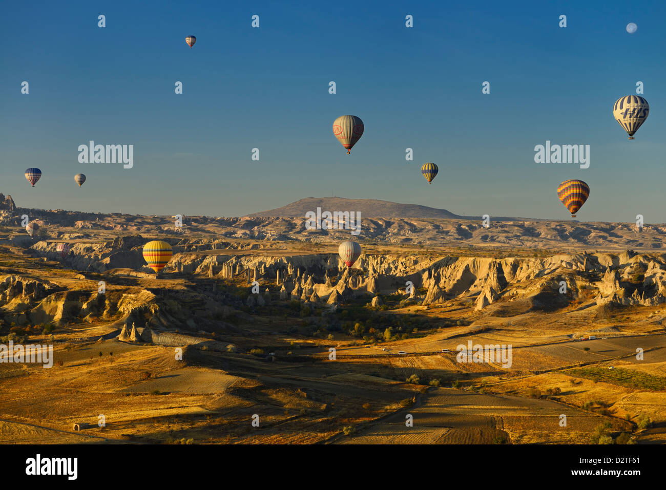 Goreme Love Valley and farm fields Cappadocia Turkey in the morning with hot air balloons and moon - Stock Image