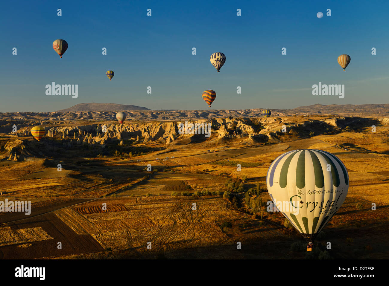 Love Valley and farm fields at dawn Cappadocia Goreme National Park Nevsehir Turkey with hot air balloons and moon - Stock Image