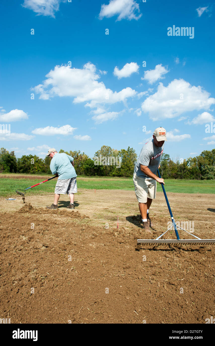Men raking soil to plant a garden - Stock Image