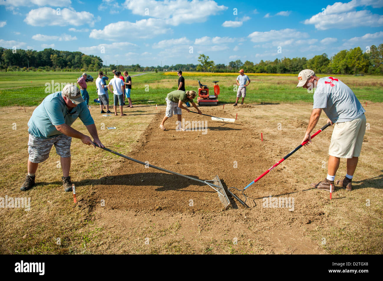 Group of people raking soil to plant a garden - Stock Image