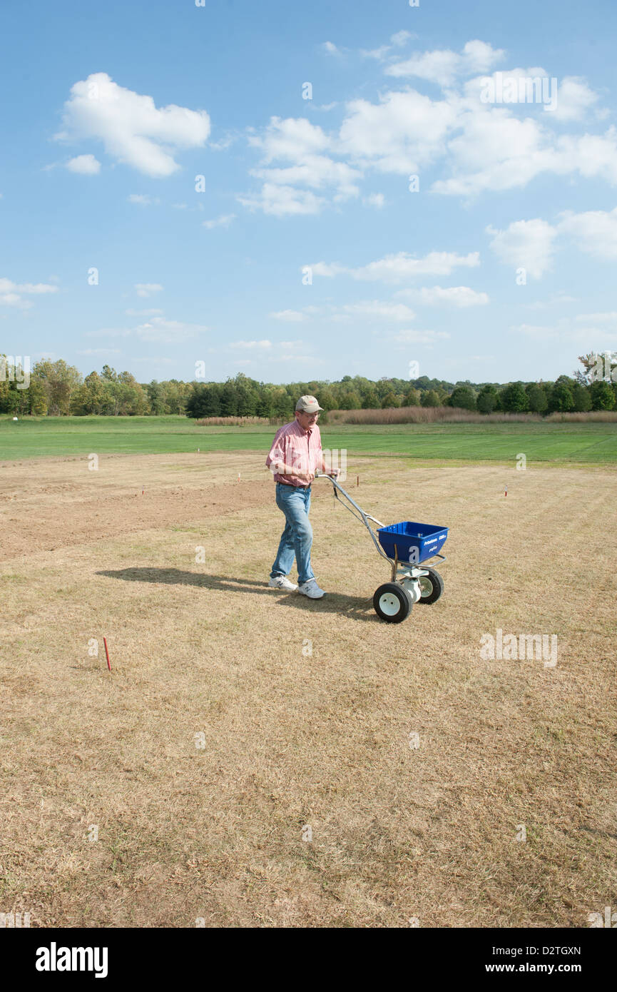 Man raking soil to plant a garden - Stock Image