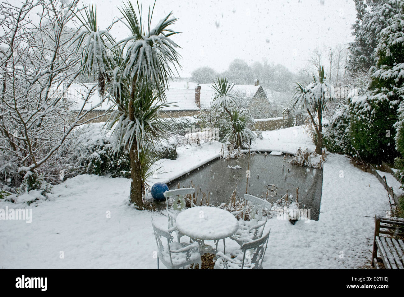 Garden pond, table, chairs & shrubs in a heavy snow storm, Devon, - Stock Image