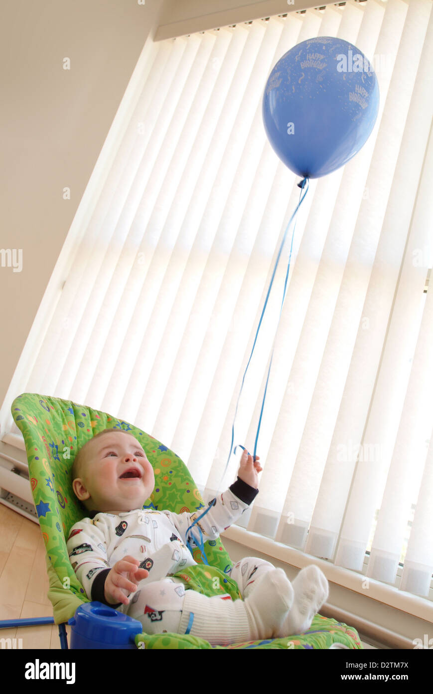Baby with a blue baloon - Stock Image