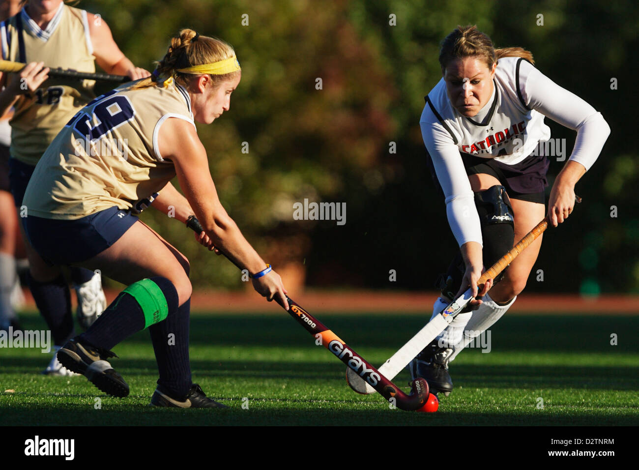 A Catholic University player (R) and Juniata College player (L) vie for the ball during a field hockey game. - Stock Image