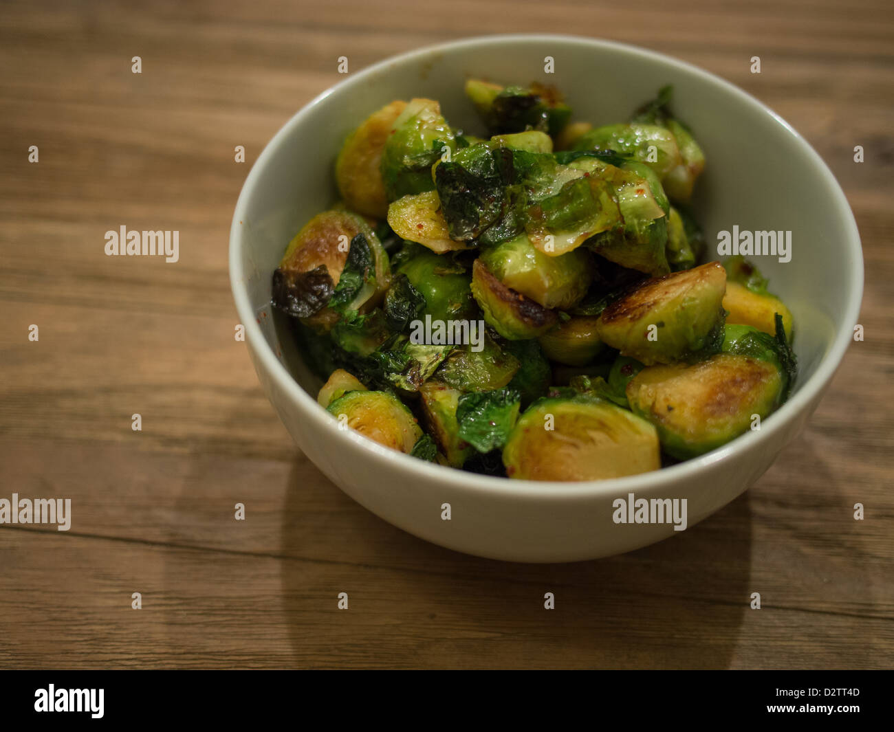 Grilled Brussel sprouts in a bowl on a wooden table - Stock Image