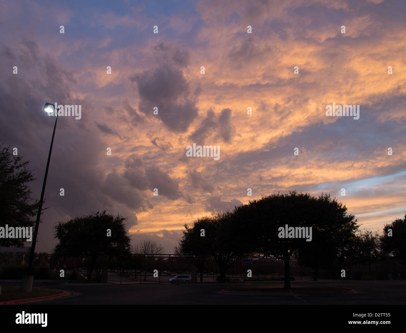 Purple and pink fluffy clouds over a parking lot at sunset - Stock Image