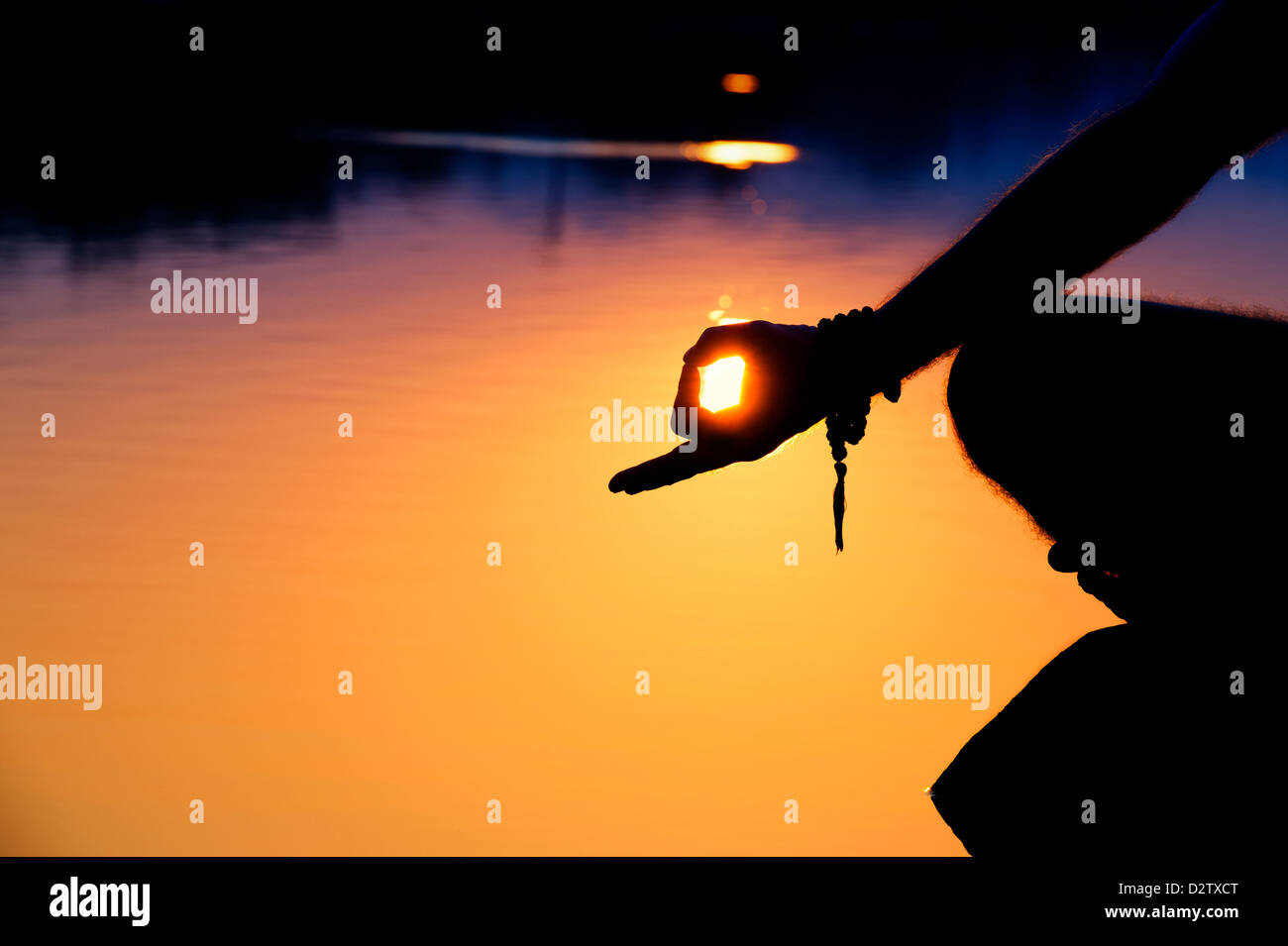 Sunrise silhouette of a mans hand whilst meditating on rocks at an Indian lake. Andhra Pradesh, India - Stock Image