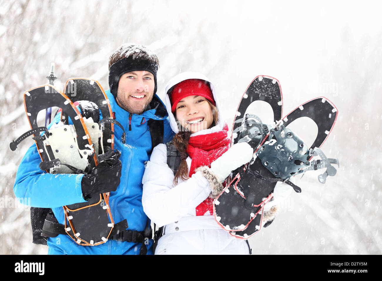 Portrait of young smiling active mixed race winter couple holding snowshoes hiking in snow - Stock Image