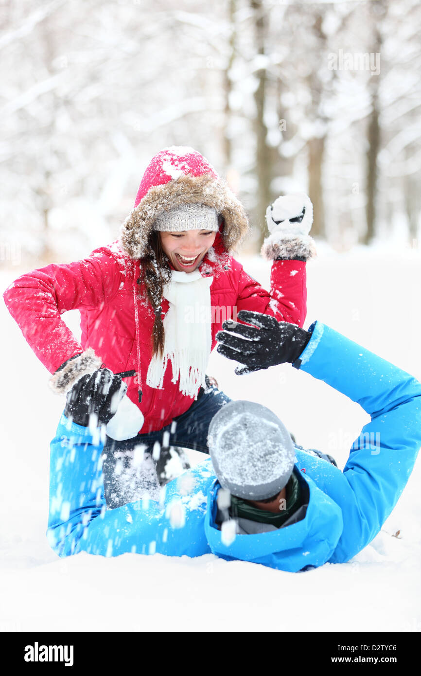 Winter couple snowball fight. Young couple having fun in snow outside. young couple in their twenties - Stock Image