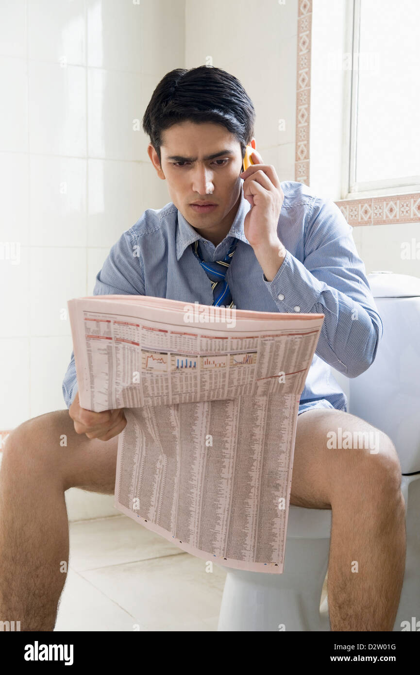 Young Man Using Laptop On Toilet. Stock Image - Image of