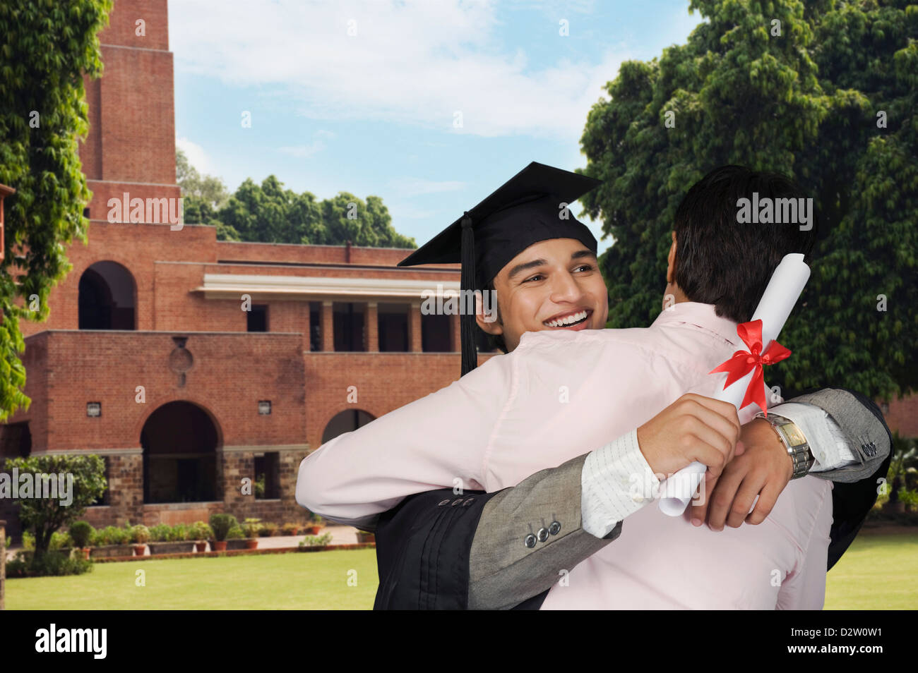 Student hugging his father after getting diploma - Stock Image