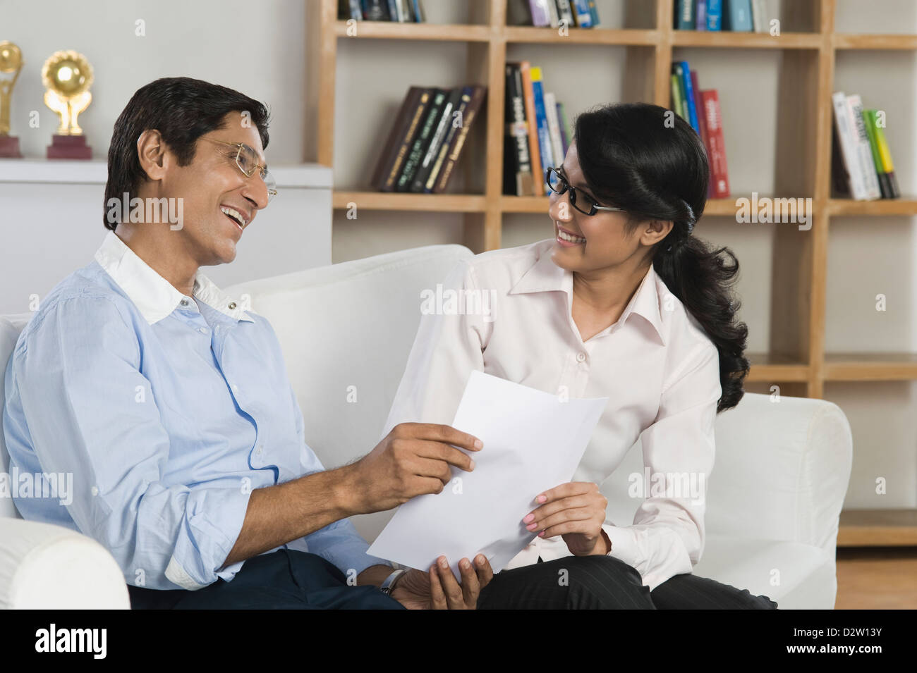 Man looking the report card of his daughter and smiling - Stock Image