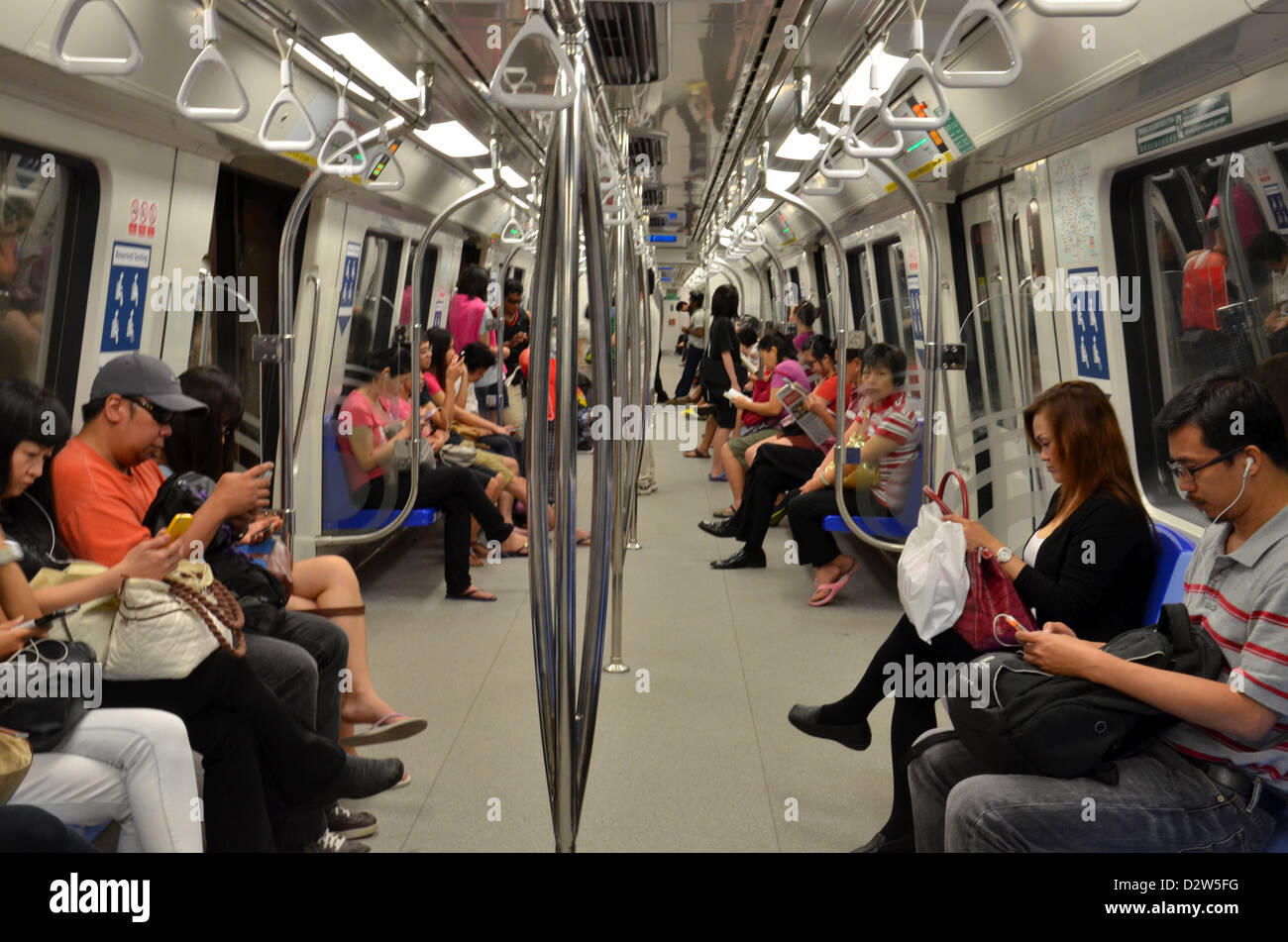 Travelers sitting inside a Singapore MRT subway train ...