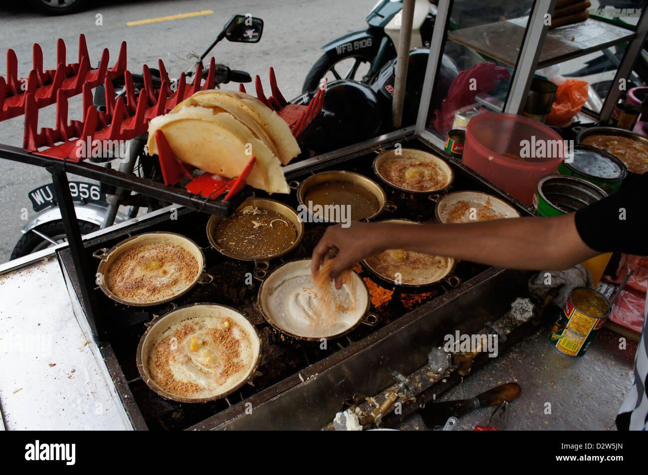 hawker making Apam balik (turnover pancake) Malaysian pancake with sugar, peanuts and creamy sweet corn fillings - Stock Image