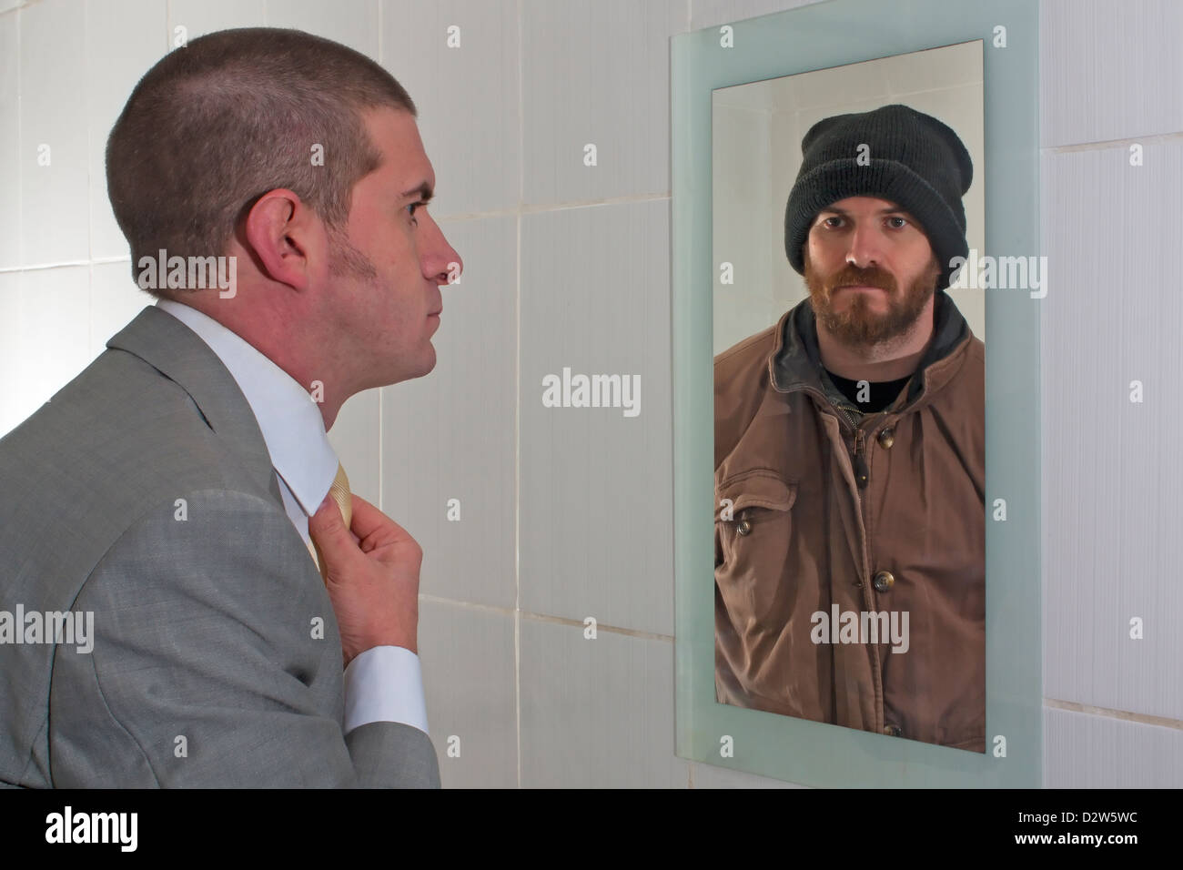 Business Man looking in the mirror and seeing a Tramp staring back in the reflection - Stock Image