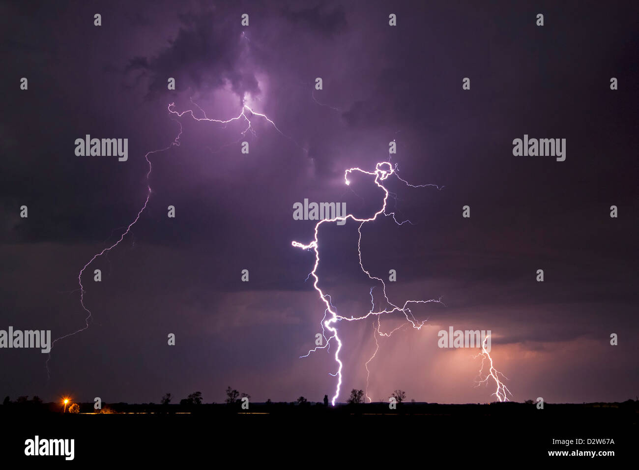 Lightning bolts lighting up the sky over a rural landscape - Stock Image