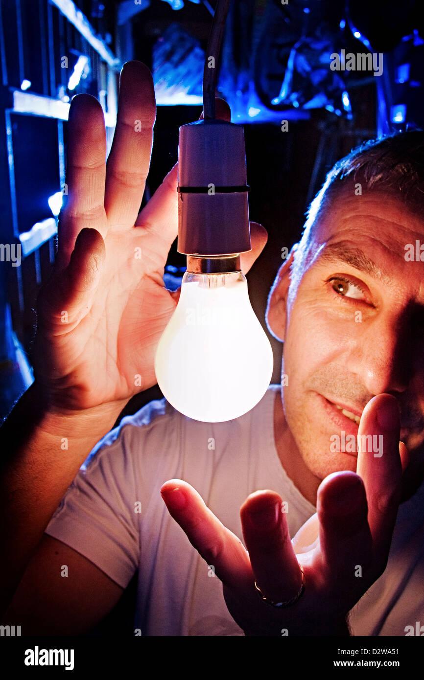 Man by a 60 watt electric light bulb - Stock Image