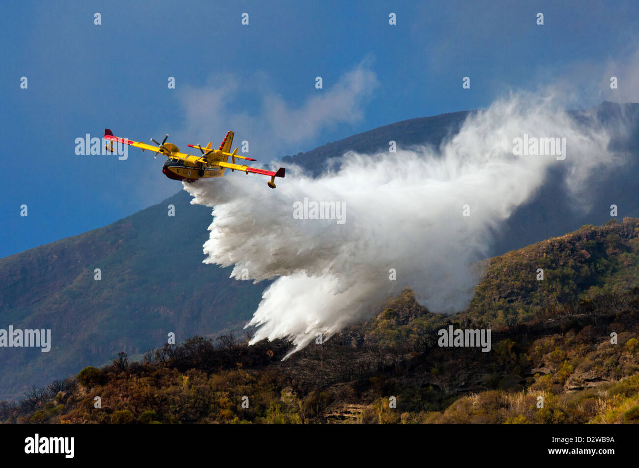 Canadair fire fighting plane flying over Stromboli island trying to extinguish a fire in Sicily, Italy. - Stock Image