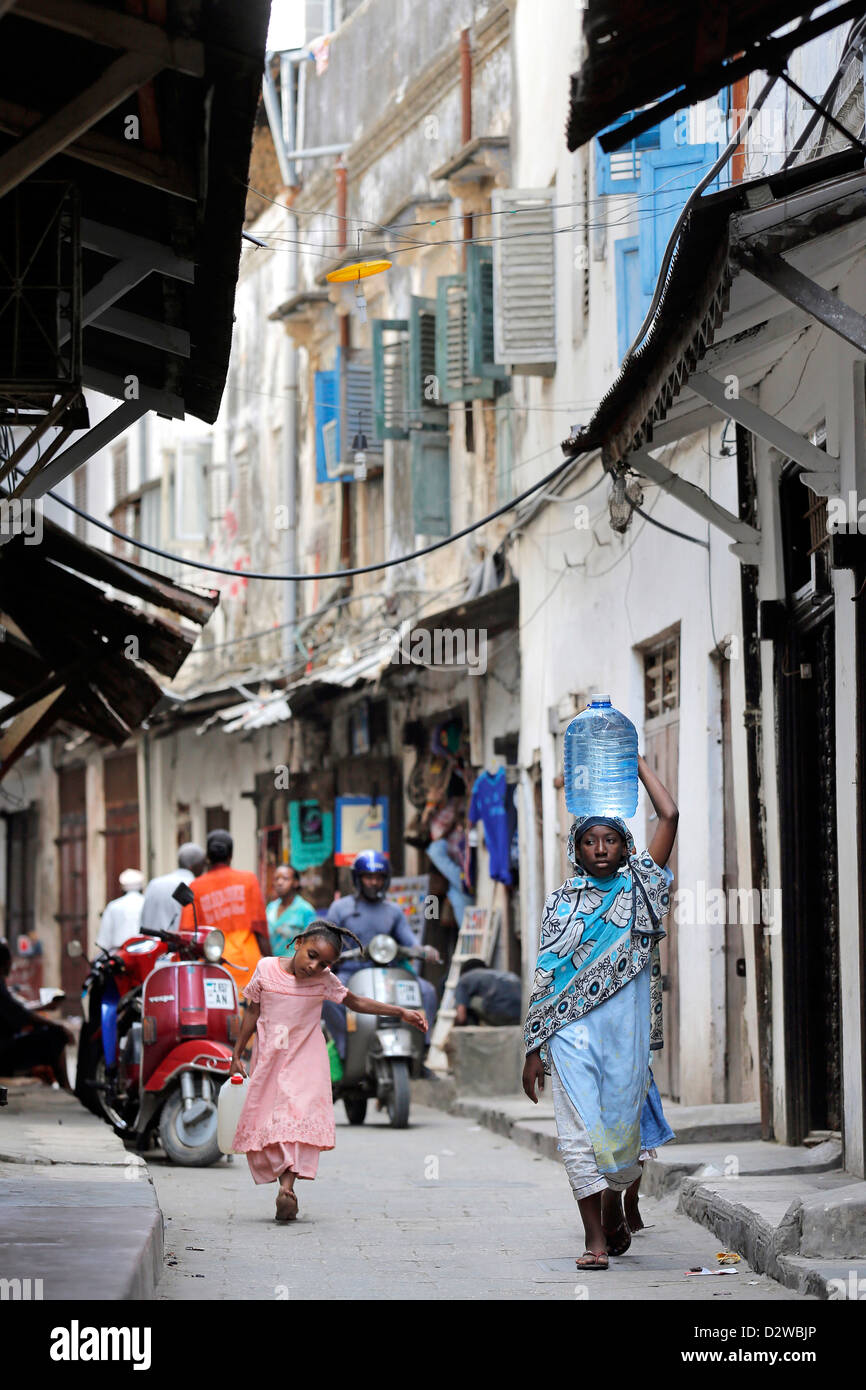 People in a narrow street in Stonetown Zanzibar, Tanzania - Stock Image