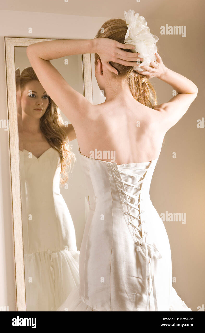 A pretty young bride looking at her reflection in a mirror as she ...
