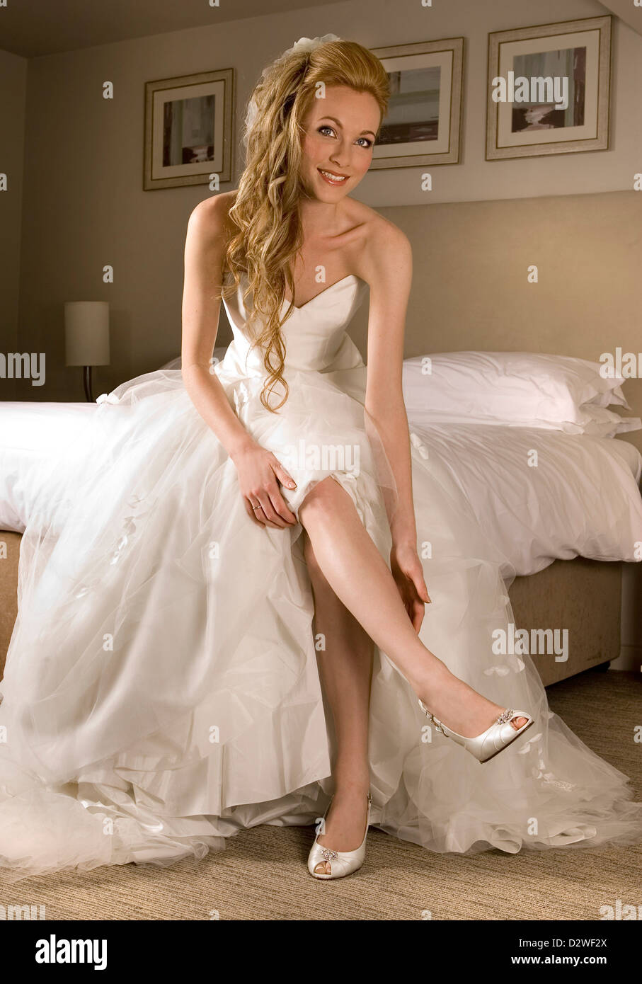 A Happy Looking Bride Sitting On The Edge Of Her Bed In