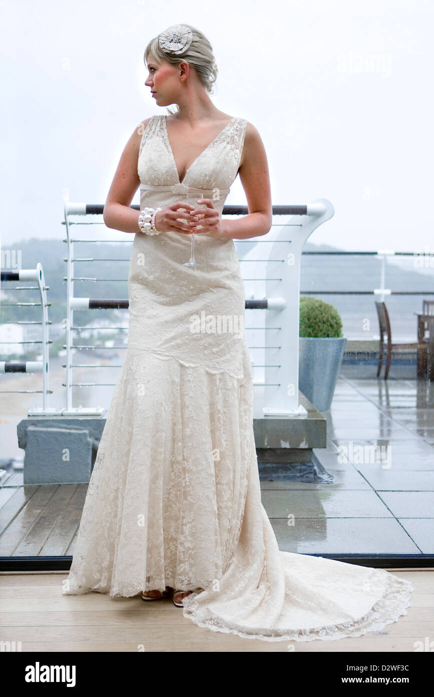 A pretty young blond bride looking out of a window as she waits for her wedding ceremony. Stock Photo
