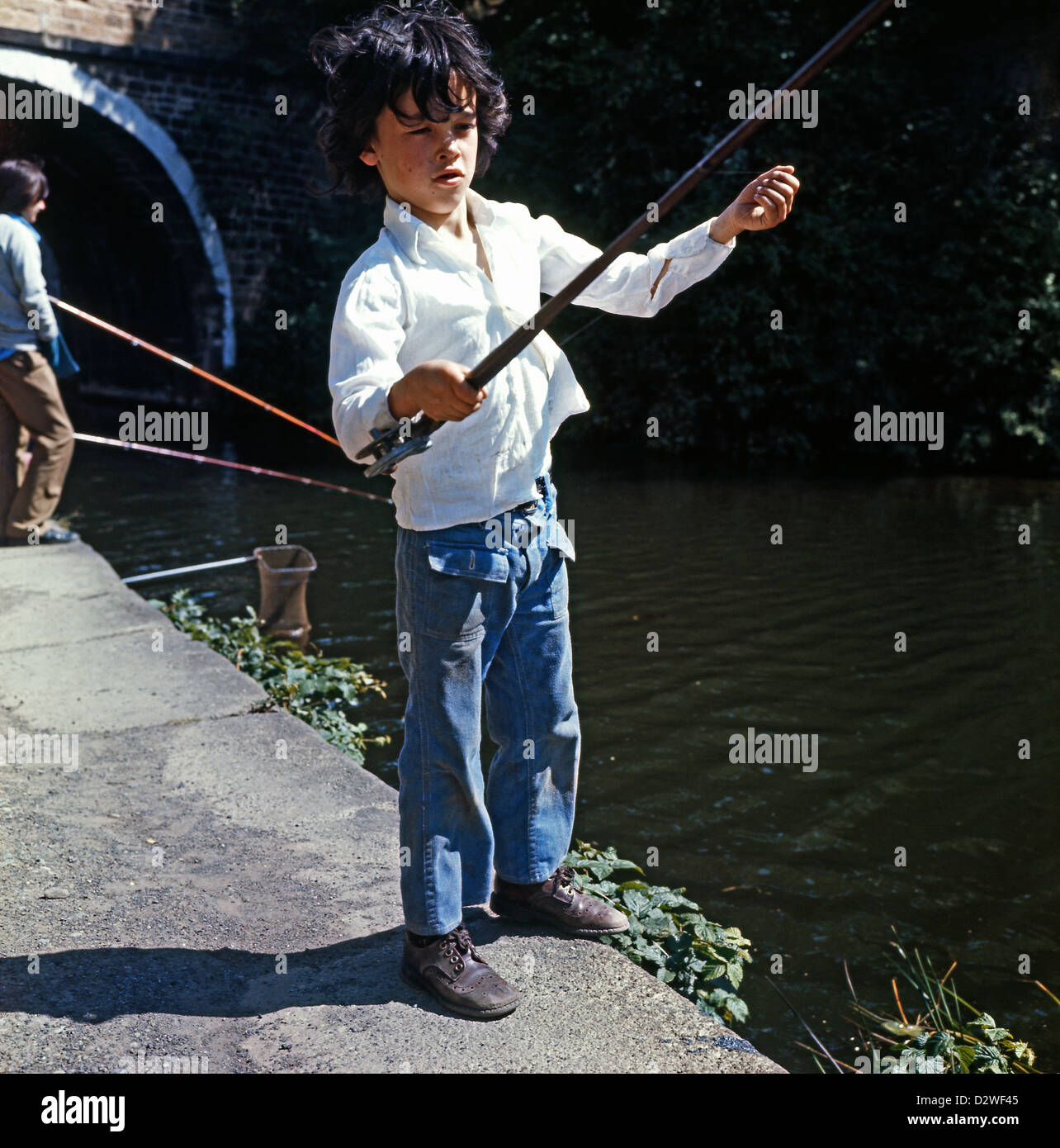 Young boy fishing on the Leeds & Liverpool Canal  by the Armley Mills Bridge, West Yorkshire 1974 Great Britain Stock Photo