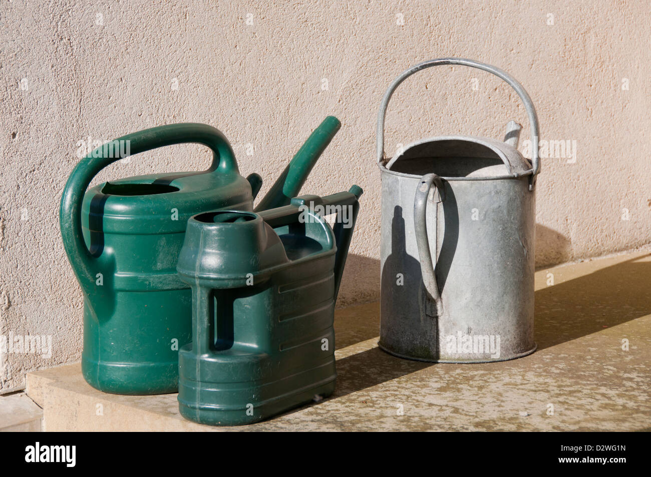 two plastic and one galvanized steel watering can - Stock Image