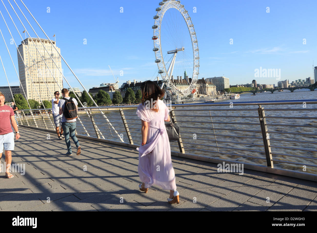 Crossing the pedestrian Golden Jubilee Bridge over the river Thames with the London Eye behind on the South Bank, - Stock Photo