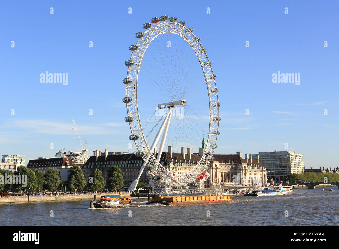 Cargo ships passing the London Eye while travelling on the River Thames on a summer's evening, in England, UK - Stock Image