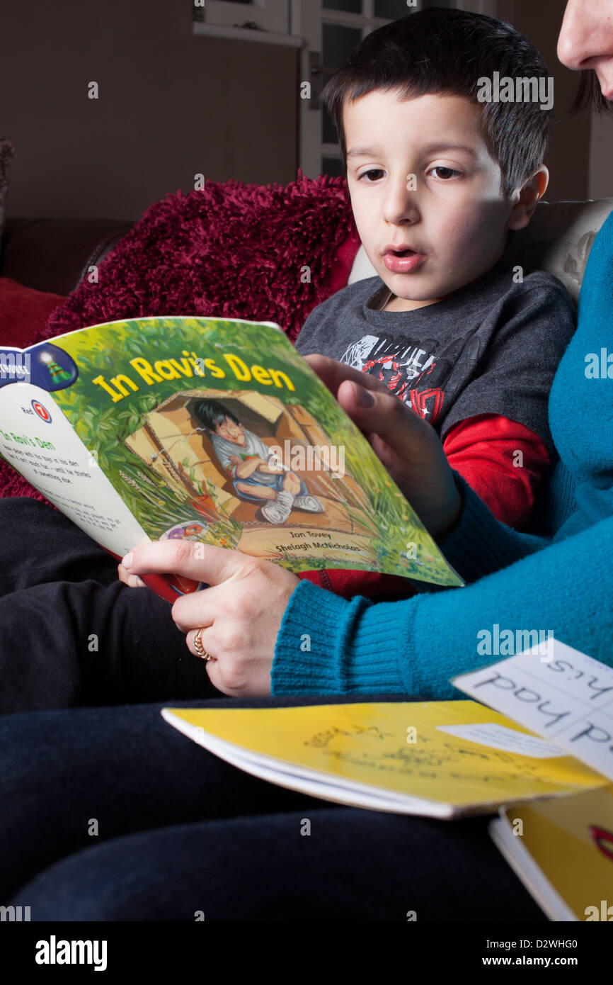 Mother helps 5 years old child to read a book Stock Photo ...