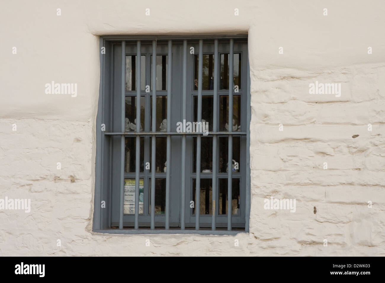 A barred window in an old building near Old Fisherman's Wharf in Monterey, California. - Stock Image