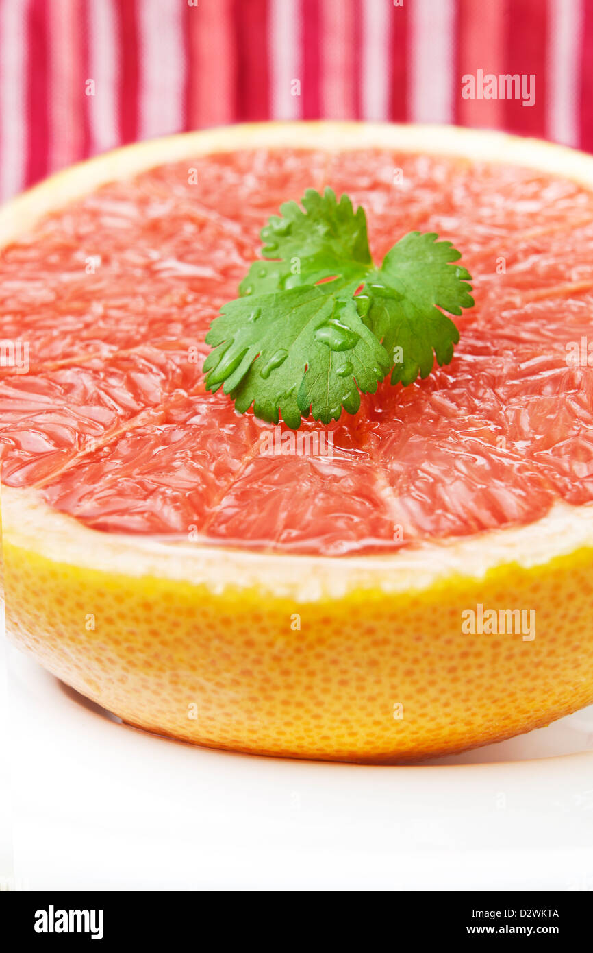 Half pink grapefruit freshly cut with coriander leaves. - Stock Image