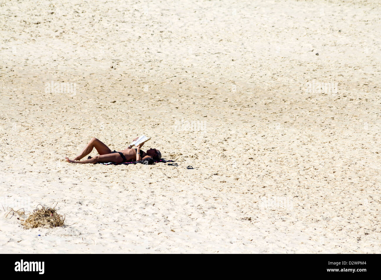 Woman sunbathing on a deserted beach in Australia - Stock Image