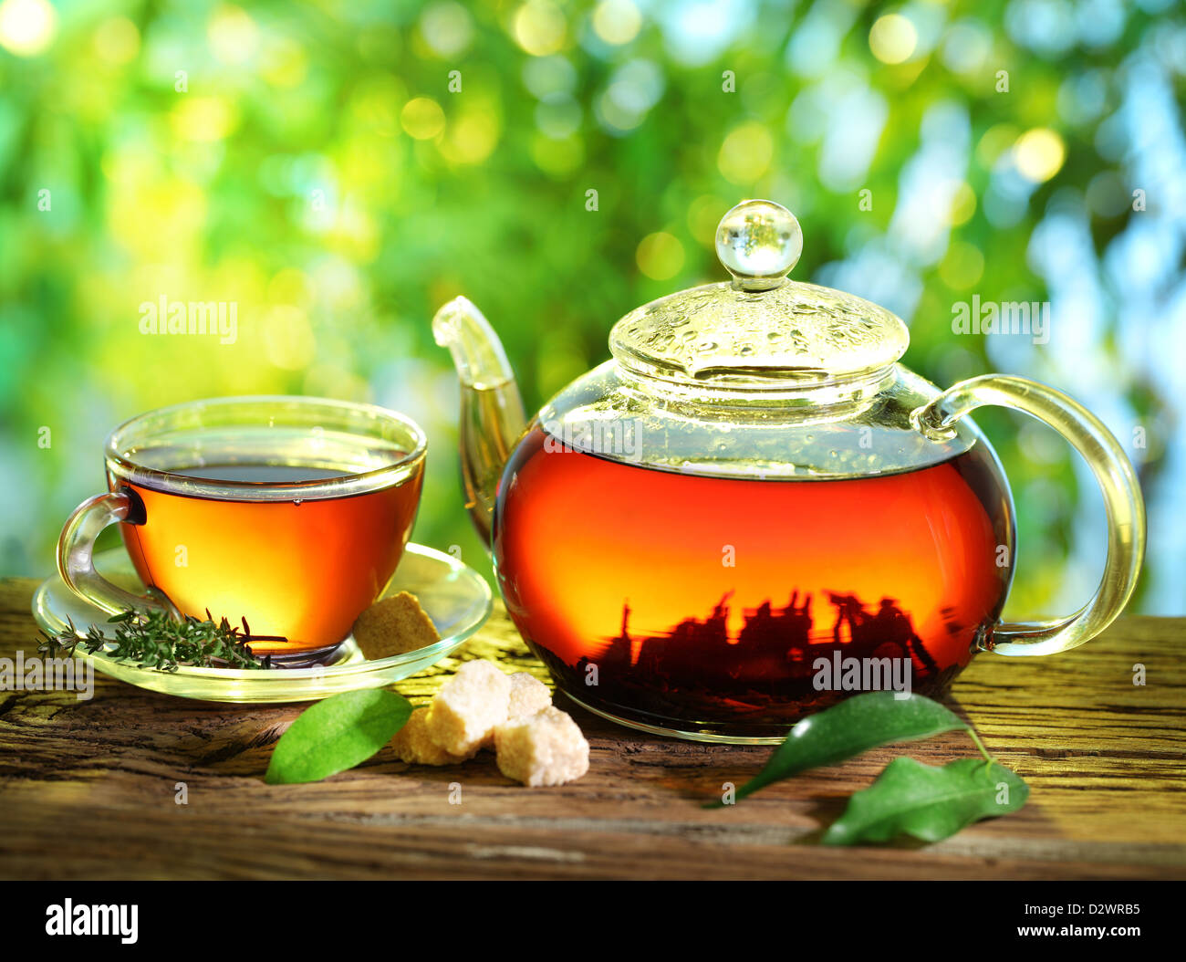 Cup of tea and teapot on a blurred background of nature. - Stock Image