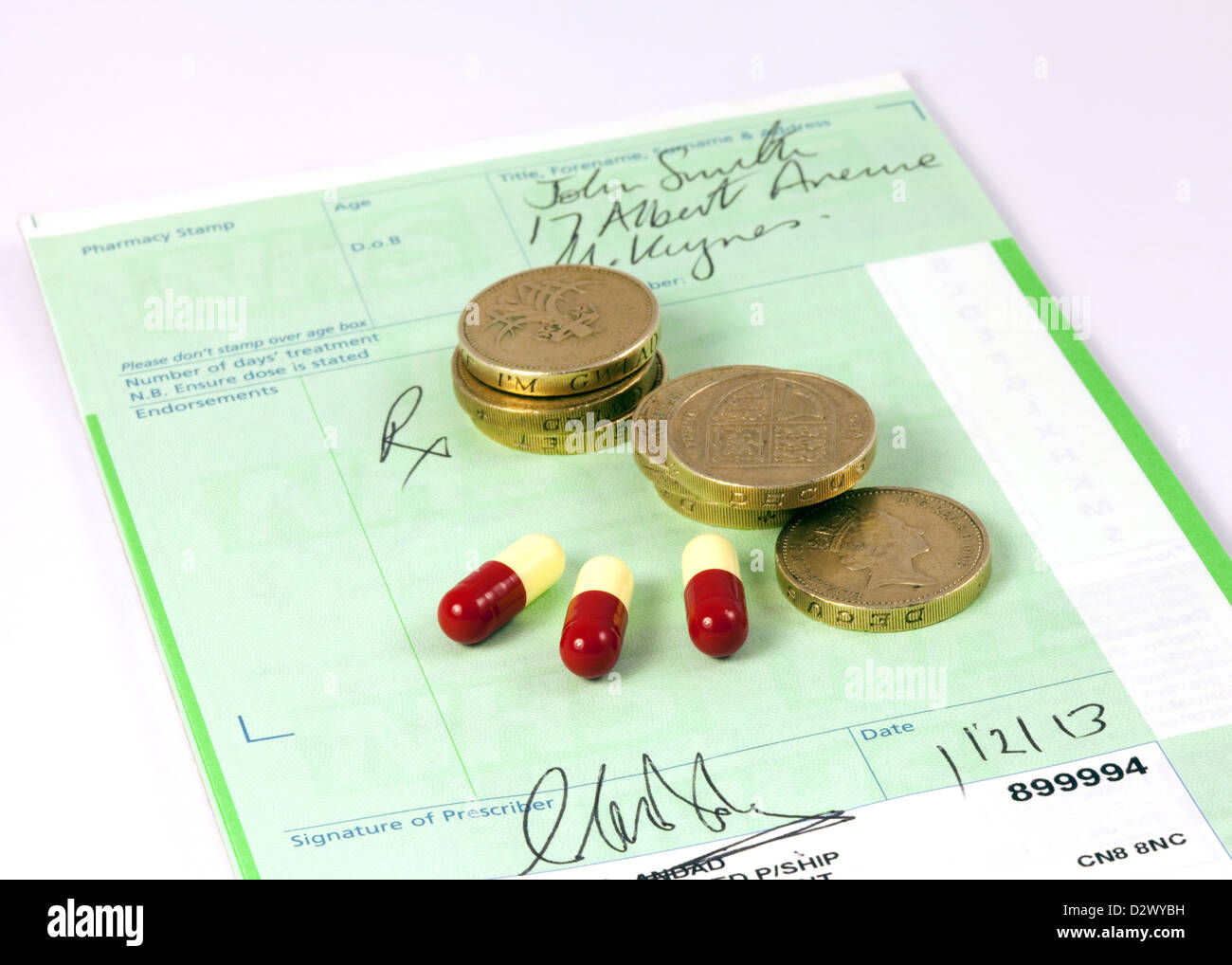 NHS prescription with pound coins and drugs to illustrate the concept of prescription drug costs, UK - Stock Image