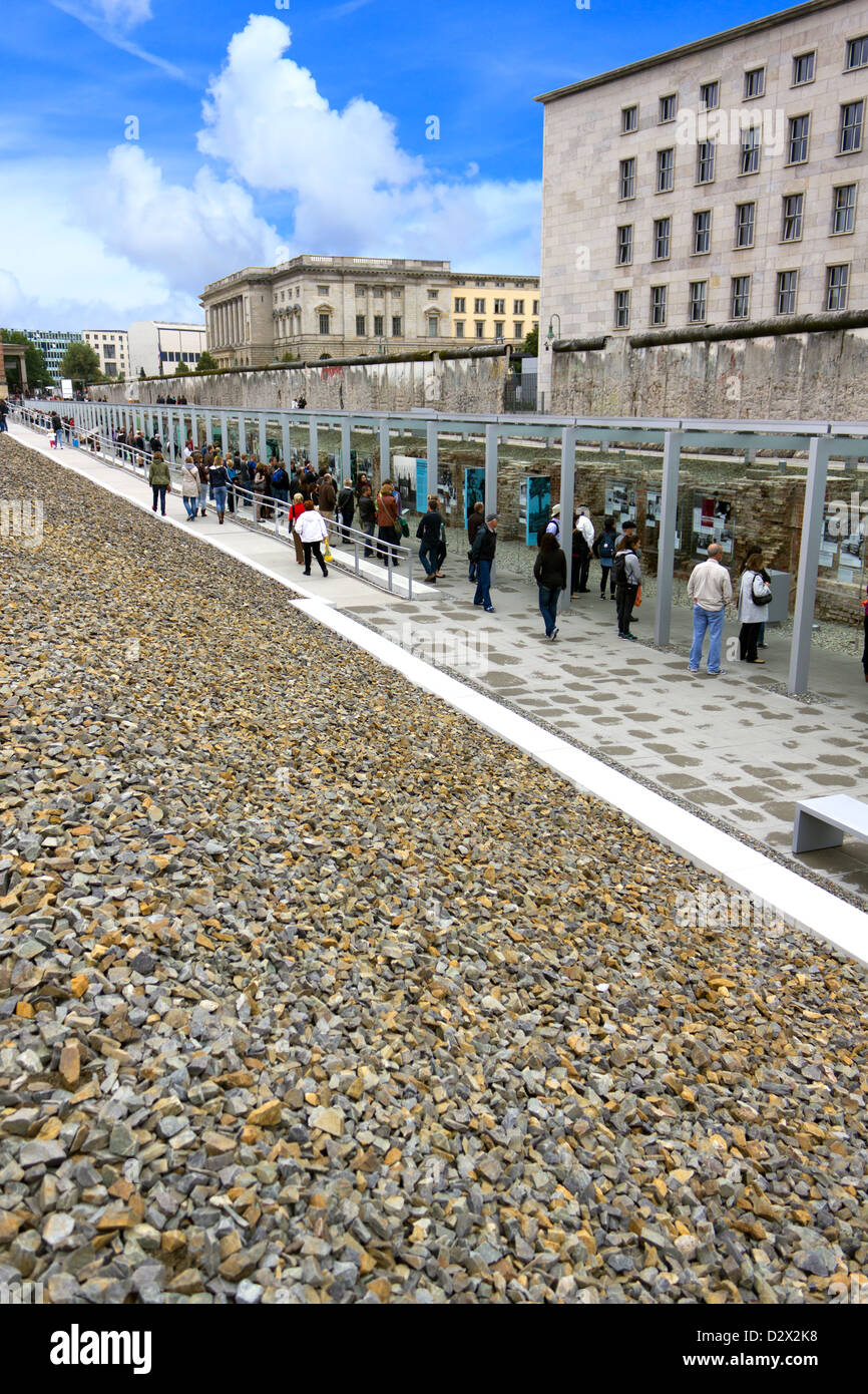 Tourists flocking to see the remains of Berlin wall with photo exhibition display. Stock Photo